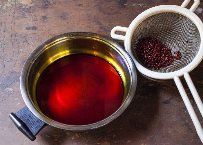 In a saucepan, combine the the oil and annatto. Heat on low-medium heat for 5 to 7 minutes or until the oil turns a bright red. Stir now and then and don't let it boil.