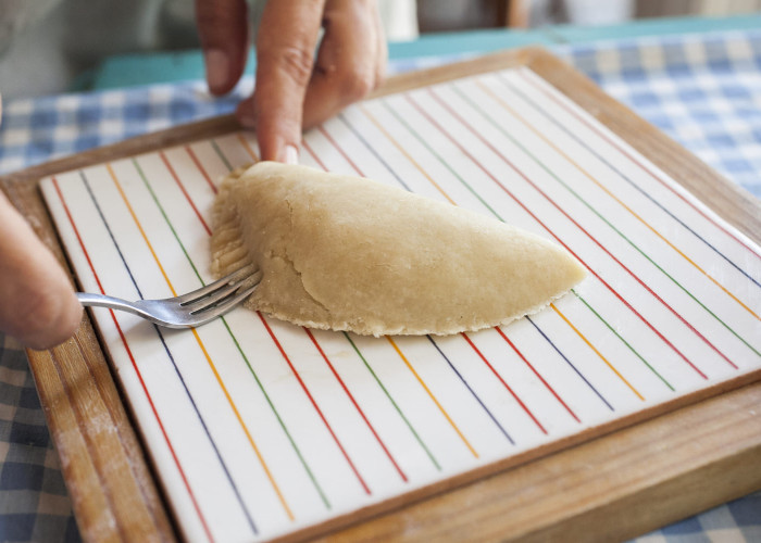 Fold the dough over the filling and seal the empanada. Using a fork, or your fingers, press edges together to seal.
