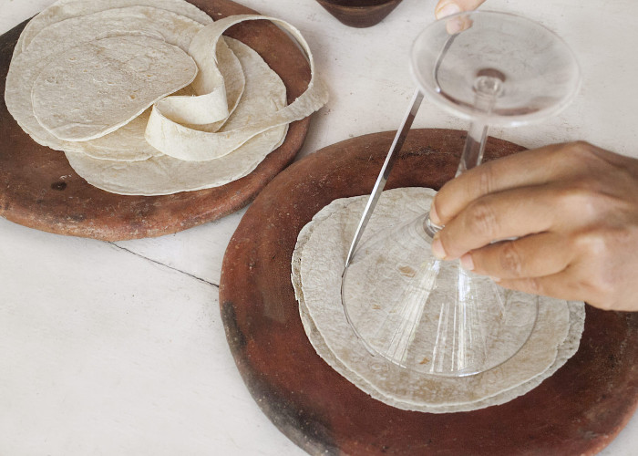 Take the tortillas and cut 4-inch diameter circles (a standard margarita glass is about the right size for measuring, and a pizza cutter gets the job done quickly). You can bake the leftover tortilla bits to make chips.
