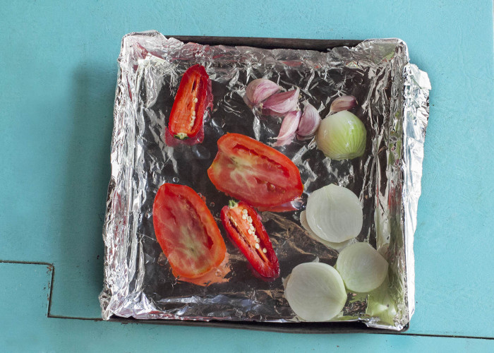 For the sauce, preheat the oven to 400 ºF. Line a baking sheet with foil paper. Add all the tomatoes, peppers and onion, cut-side up. Drizzle with olive oil, season with salt and pepper. Remove all the cloves from the bulb of garlic (leave the skins on) and nest it in a foil packet, adding a little oil before closing. Transfer to a baking sheet. Roast for 1 hour, rotating the baking sheet halfway through cooking time. Remove from oven and let cool.