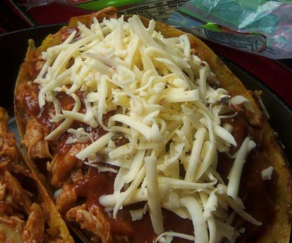 To each, add 1/4 cup of enchilada sauce and a little more salt and pepper. Stir to combine. Top each with shredded chicken, more enchilada sauce and shredded cheese. Sprinkle on a little crushed oregano. Bake for 25 minutes then place under broiler just to brown the cheese a little. Serve on a bed of lettuce and garnish with sour cream, pico de gallo and lime wedges.