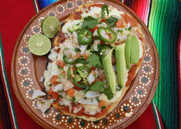Remove pizza from the grill onto a large cutting board. Right before serving, using a slotted spoon, divide the shrimp ceviche onto the 4 pizzas. Garnish with avocado, hot sauce, cilantro, jalapeño and lime wedges. Slice into quarters for appetizers or serve as individual pizzas for 4.