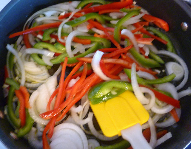 In a large frying pan or pot, heat the olive oil, add garlic and sautee until golden then add onion and peppers cooking them until wilted.