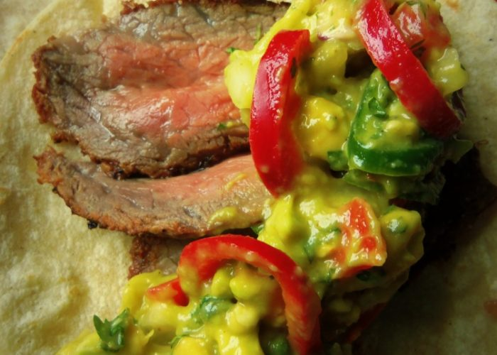 While steak is resting, heat the tortillas on the grill. Slice the steaks, against the grain, into thin slices. Serve 2 stacked tortillas per taco with some freshly made guacamole. Yields up to 4 servings, 2 tacos per person.