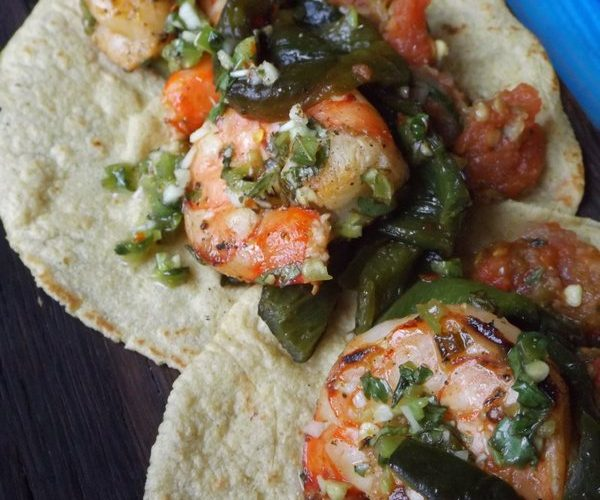 Transfer cooked shrimp to the bowl with reserved marinade. Add the poblano strips to hot pan just to warm up. Combine poblanos with shrimp. Toss all together to combine. Serve on warm corn tortillas with fire roasted salsa.