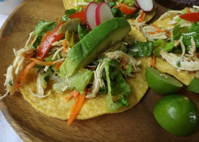 Fold in the lettuce right before serving. Serve the salpicón over corn tostadas. Garnish with radishes, avocado, hot sauce and lime.