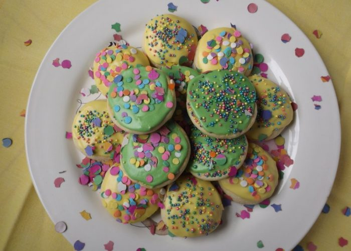 To the remaining frosting, add a few drops of blue food coloring until desired green color. Frost remaining cookies and add sprinkles.
