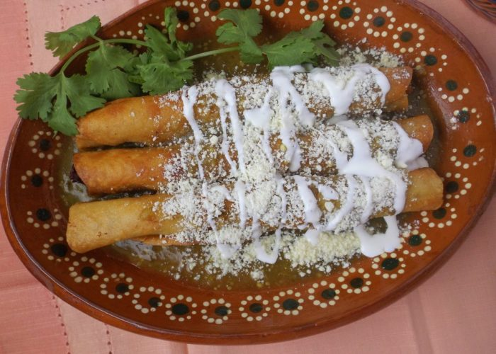 While the flautas drain and cool slightly, warm the salsa verde in a saucepan for a few minutes. To plate, add two extra long flautas to a plate. Ladle on a generous amount of warm salsa. Garnish with crema and queso cotija.