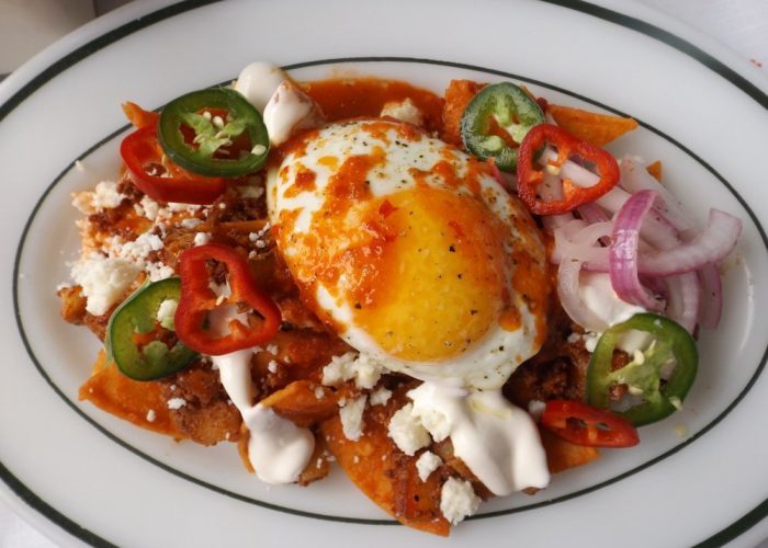 To the remaining salsa, fold in the crispy chips until evenly coated. Divide the chilaquiles onto four plates. Top with chorizo and potatoes. Garnish with queso fresco, crema, onions, sliced jalapeños and egg. Spoon on a little of the reserved salsa onto egg. Serve right away with a side of your favorite refried beans.