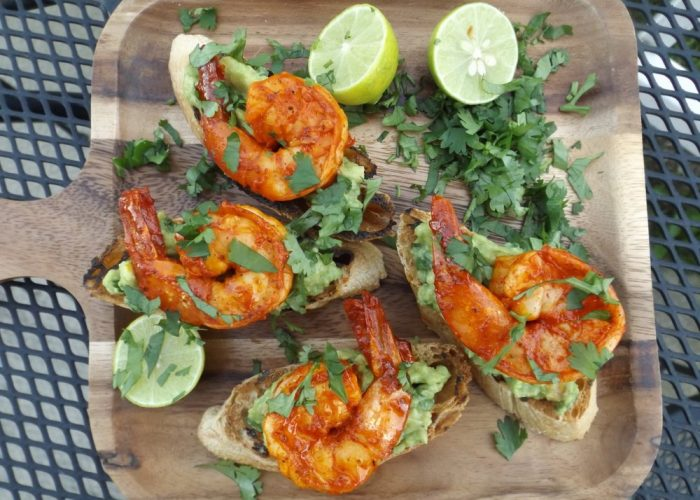 Toast the crostini bread slices on hot grill just until you get some grill marks. Transfer to serving plate or platter. Top each crostini with guacamole and then shrimp. Garnish with chopped cilantro and lime.