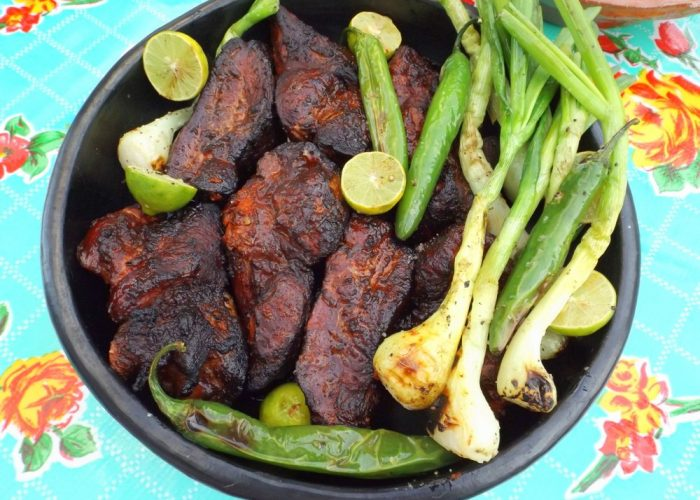 Remove ribs from heat and let rest for 20-30 minutes. At this time, grill spring onions, serranos and lime halves for a few minutes. Turn as needed. Serve with warm tortillas and salsa.