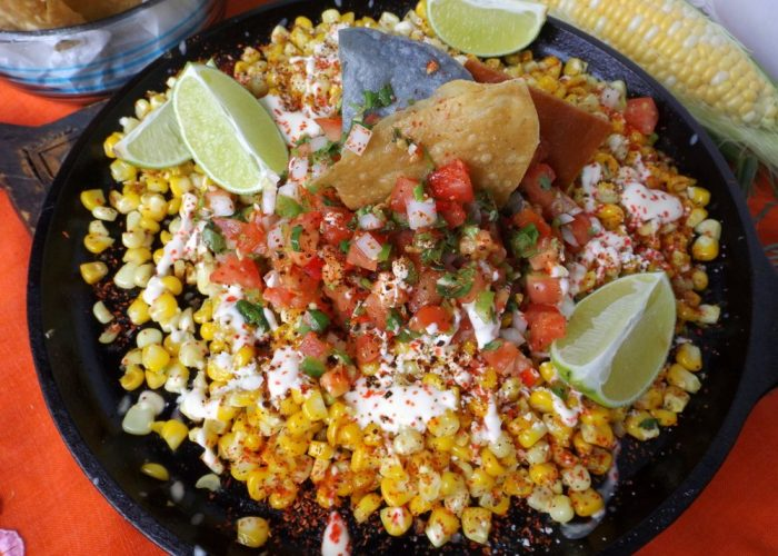 Cook until you get the desired look for the corn. If you like darker toasting, then leave it on a little longer. To plate, you could leave the toasted corn in the pan or you can serve it on individual plates. Top with some of the fresh salsa in the center. Drizzle on some of the crema and sprinkle on some of the cotija cheese and chile limón seasoning. Serve with lime wedges and tortilla chips.