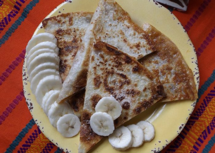 Transfer quesadillas to a cutting board. Sprinkle lightly with cinnamon and sugar. Let cool for a few minutes. Use a large straight edge knife or pizza cutter to slice quesadilla into 4 wedges. Serve with extra banana slices and dulce de leche.