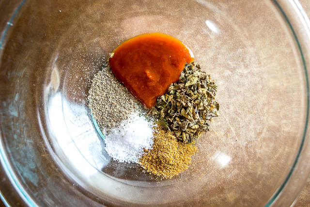 In a mixing bowl combine the spice rub ingredients:  2 teaspoons oregano, 1 teaspoon cumin, 1 tablespoon adobo sauce, 2 teaspoons salt, freshly cracked pepper, and a dollop of olive oil.