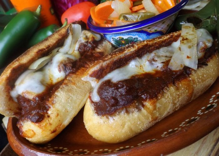 Preheat broiler on high. For the torta, slice your bolillos open and remove just a little of the bread inside. To each bolillo, carefully add 3 meatballs. Spoon in some sauce. Add 2 ounces of cheese to each one. Place on baking sheet or pan, open side up. Place under broiler just until cheese melts. Serve with grilled jalapeños and onions.
