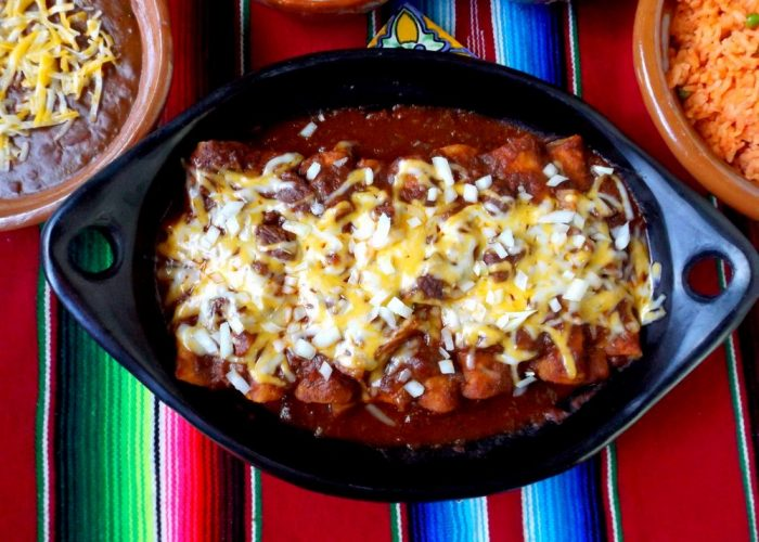 To finish, ladle the brisket chili over the top of enchiladas in baking dish. Try spreading the sauce so it covers tortillas generously. Then concentrate the beef and potatoes towards down the center/top of the enchiladas. Add cheese and bake in preheated oven for 25-30 minutes or just until cheese melts. Remove from oven and garnish with more remaining diced onions. Serve right away.