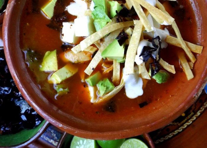 To serve, add a generous handful of fried tortilla strips to the bottom of bowl. Ladle in some of the chicken and broth, enough to cover tortilla strips. Garnish with a few more strips, cheese, avocado, crema, fried chile pasilla and lime.